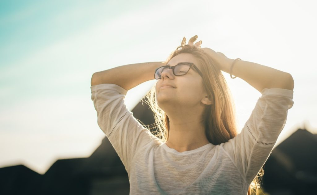 A girl wearing glasses looking into the sunshine practicing meditation and mindfulness